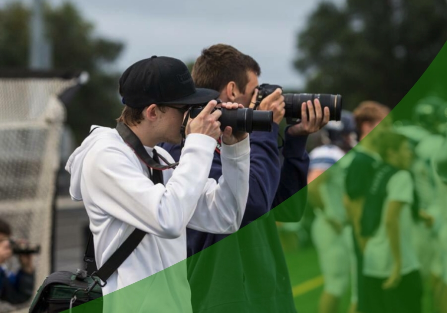Two students with DSLR cameras taking photos at a football game