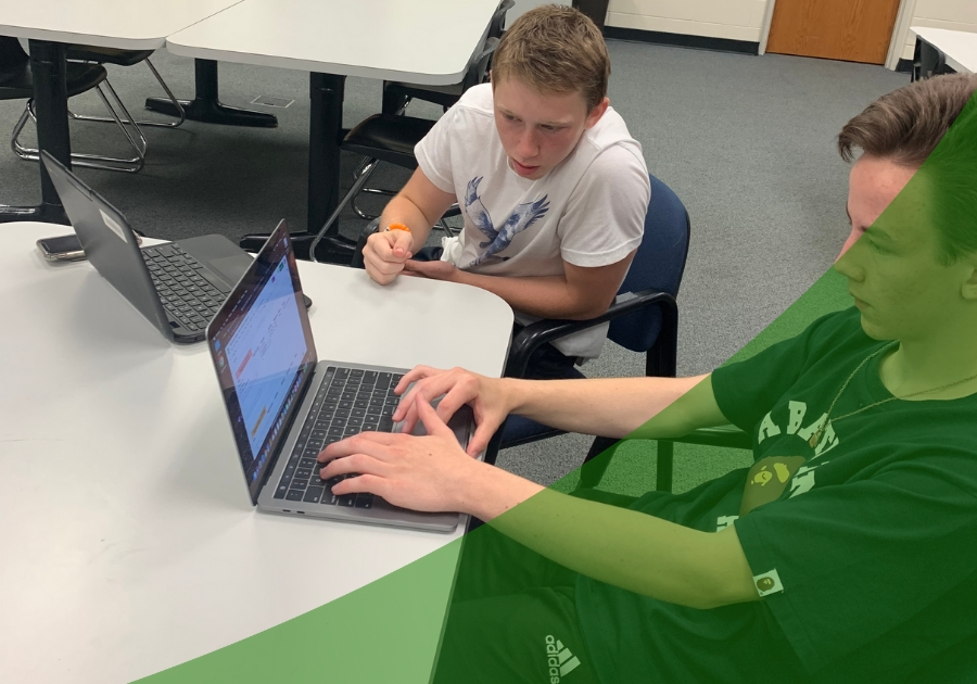 Two students working on creating content with laptops in the library with a green swoosh in the lower right corner