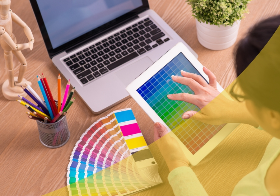 Woman holding ipad with color grid on table and laptop on a desk with colored pencils and color grid