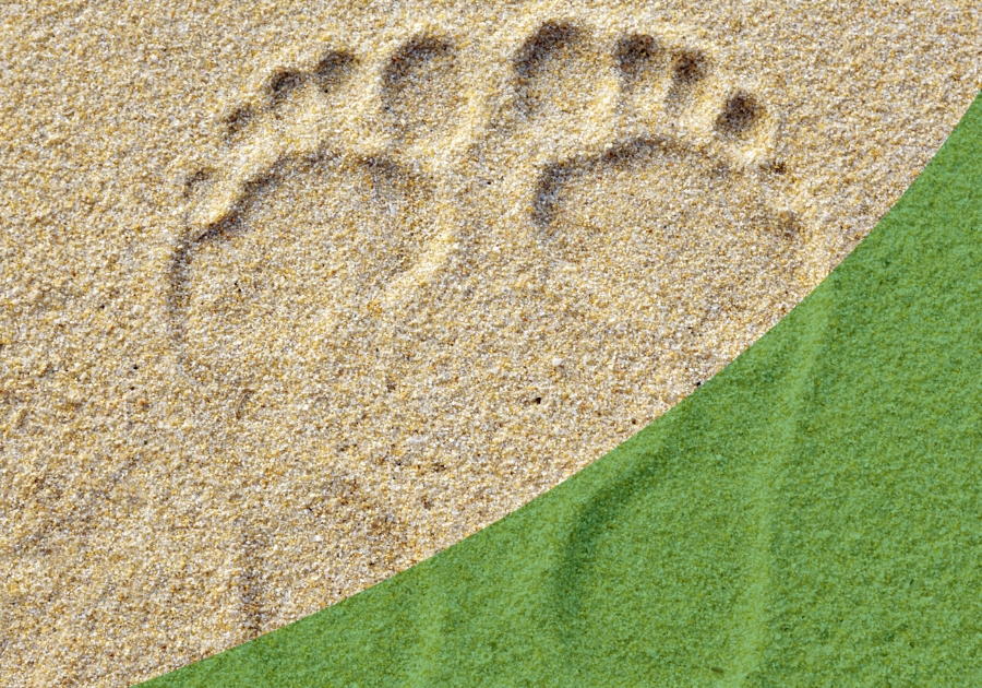 Foot prints in sand with a green swoosh over the bottom right