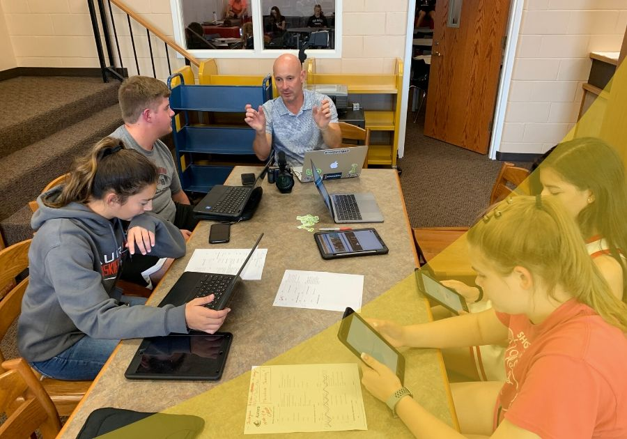 Students sitting at a table in the library of a school with devices working on creating content