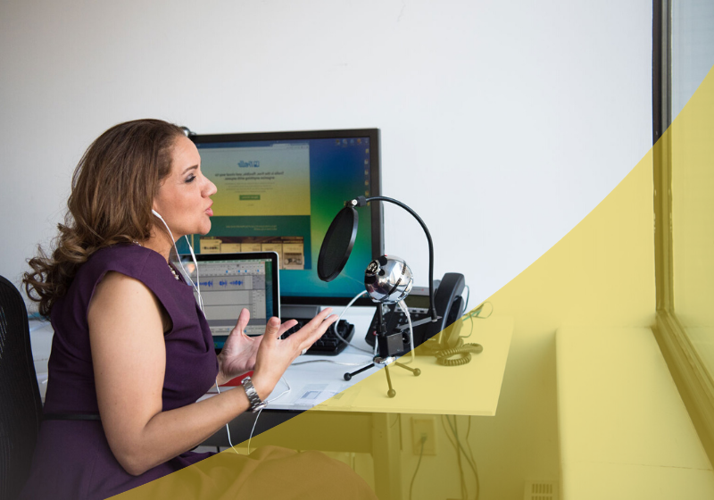 Woman speaking into a microphone at her desk with laptop and podcasting setup